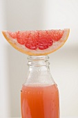 Pink grapefruit juice in bottle with fresh grapefruit wedge
