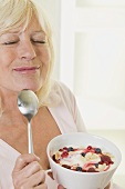 Woman enjoying yoghurt with berries and flaked almonds