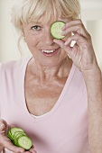 Woman holding a slice of cucumber in front of her eye