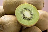 Half a kiwi fruit on several whole kiwi fruits (close-up)