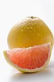 Rosa Grapefruitschnitz vor ganzer Grapefruit