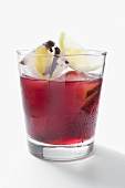 Red wine punch in glass with ice cubes and lemon