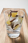 Ice cubes with spices and pieces of fruit in glass
