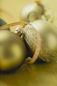 Green and gold Christmas baubles with ribbon
