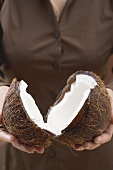 Woman holding halved coconut