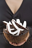 Woman holding pieces of coconut in hollowed-out coconut