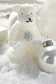 Christmas decoration: polar bear & Christmas baubles in snow