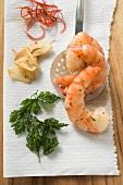 Garlic prawns on slotted spoon, ingredients beside it
