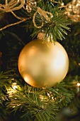 Gold bauble on artificial Christmas tree