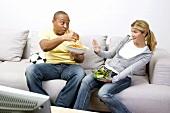 Paar vor dem Fernseher mit Erdnussflips und Salat