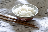 Rice in Asian bowl on newspaper, chopsticks beside it