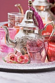 Silver teapot, glasses, roses and windlights on tray