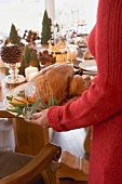 Woman serving roast turkey (Christmas)