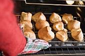 Hand holt frisch gebackene Popovers aus dem Backofen
