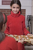 Girl serving platter of appetisers (Christmas)