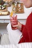 Frau hält Glas Campari mit Eiswürfeln, Snacks im Hintergrund
