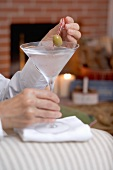 Hands holding glass of Martini with olive