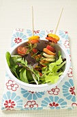 Salad leaves with mixed vegetable skewers
