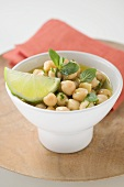 Chick-peas with lime wedge and herbs