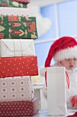 A pile of Christmas gifts, child in Father Christmas hat