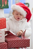 Child in Father Christmas hat opening Christmas parcel