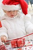 Kleines Mädchen mit Nikolausmütze öffnet Weihnachtspaket
