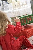 Small girl in front of a pile of Christmas parcels