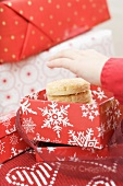 Child's hand reaching for Christmas biscuits in box