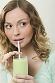 Woman drinking cucumber shake through a straw