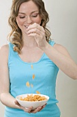 Woman dropping cornflakes into bowl