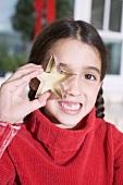 Mädchen hält ausgestochenes Plätzchen vors Auge