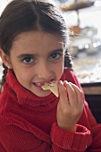 Girl eating Christmas biscuit