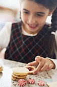 Girl taking jam biscuit from table