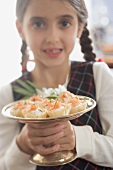 Girl holding salmon tarts on silver stand