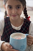 Girl holding large mug of cocoa with pieces of candy cane