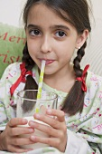 Girl drinking milk through straw