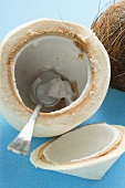 Coconut, shelled and hollowed out, with spoon