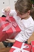 Girl opening Christmas parcel
