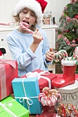 Boy in Father Christmas hat eating candy cane