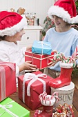 Girl and boy in Father Christmas hats exchanging gifts