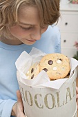 Boy looking at chocolate chip cookies in cookie tin