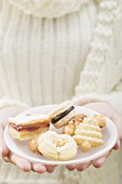 Woman holding assorted Christmas biscuits on plate