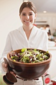 Young woman holding large bowl of salad