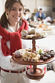Young woman holding tiered stand full of Christmas fancies