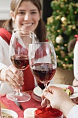 Young woman raising glass of red wine at Christmas dinner