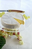 Reblochon with grapes on glass stand