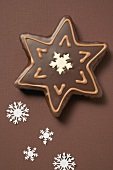 Star biscuit with chocolate icing on brown background