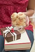 Woman holding almond biscuits and Christmas gifts