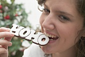 Woman biting Christmas biscuit (the word HOHO)
