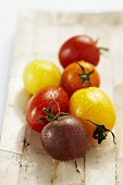 Tomatoes of various colours with drops of water